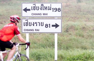 Road sign with cyclist riding past