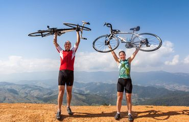 Two cyclists holding up bikes above head