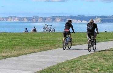 Couple riding along coastal path